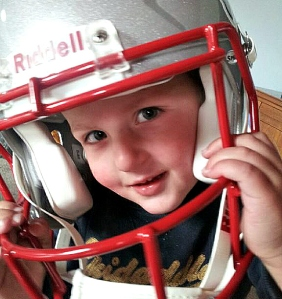 Picture of two year old trying on NFL helmet